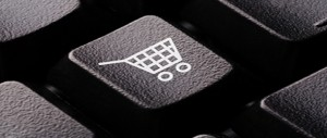 Close-up of a computer keyboard key with a shopping cart icon.