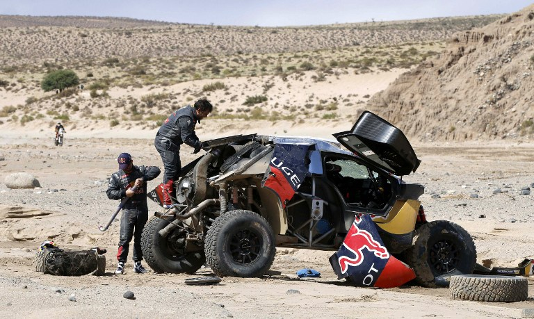 Peugeot's French driver Sebastien Loeb and his co-driver Daniel Elena after putting their overturned car back on its wheels during Stage 8 of the Dakar 2016 between Salta and Belen, Argentina, on January 11, 2016. won the stage ahead  AFP PHOTO / @world / ANDRE LAVADINHO / AFP / @world / ANDRE LAVADINHO